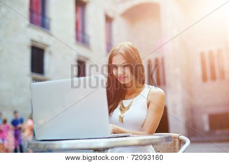 Attractive woman typing something on a laptop keyboard
