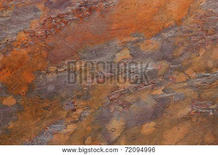 Pattern of a stone plate in orange, ocher, silver, purple