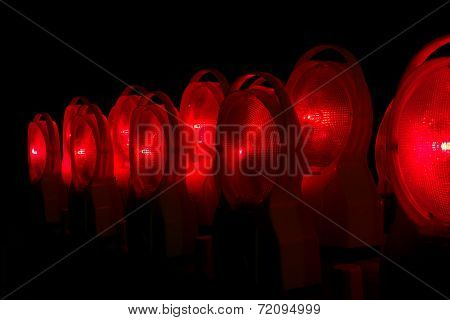 Red lighted construction sight lamps at night
