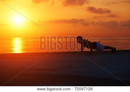 Silhouette of athletic runner warming up and doing some push ups on the beach, push ups or press ups