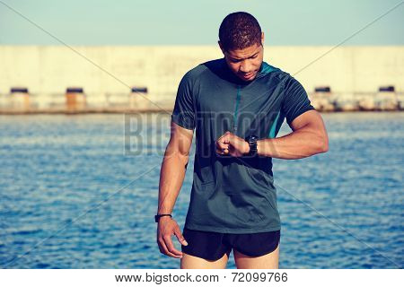 Runner looking at smart watch having rest after jogging outdoors