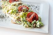 pic of shredded cheese  - A Caesar Salad with shredded parmesan cheese croutons and tomatos - JPG