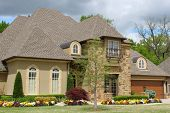 stock photo of stonewalled  - Nice brick house with pretty landscaping - JPG