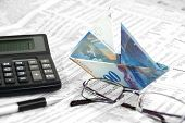 pic of deprivation  - Swiss Banknote is folded as boat on the stock paper with eye-glass and calculator