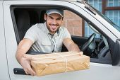 image of shipping receiving  - Delivery driver offering parcel from his van outside the warehouse - JPG