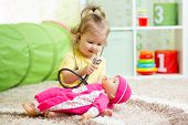 stock photo of doll  - child girl playing doctor with doll toy - JPG