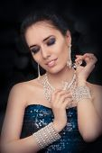 picture of perfume bottles  - Glamorous portrait of a beautiful young woman preparing for party using a vintage perfume bottle - JPG