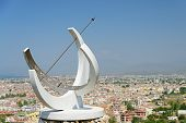stock photo of sundial  - Image of a sundial displaying roman numerals overlooking the popular european tourist destination of Fethiye in Turkey with rppm for copy space - JPG