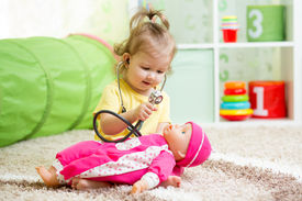 stock photo of baby doll  - child girl playing doctor with doll toy - JPG