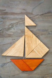 picture of tangram  - abstract picture of a sailing boat built from seven tangram wooden pieces over a slate rock background - JPG