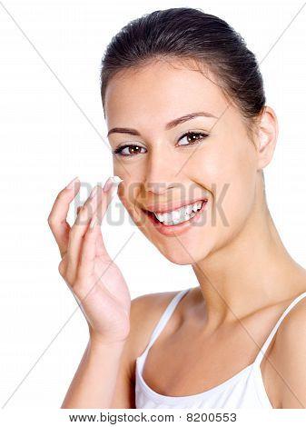 Smiling Woman Applying Moisturizer Cream