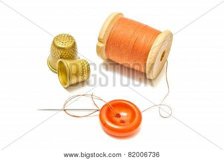 Spool Of Orange Thread, And Two Thimbles