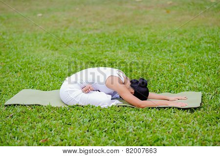 Beautiful Woman Practicing Yoga In The Park