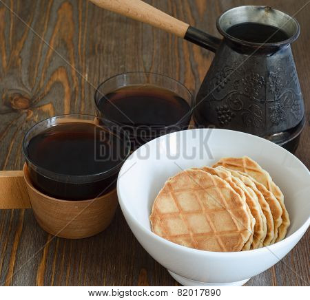 coffee, waffles in white plate and a coffee maker on a wooden background