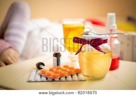 Photo Of Tea, Honey Jar And Pills Lying On Table At Bedroom
