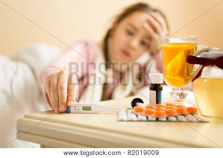 Portrait Of Sick Girl Lying In Bed And Taking Thermometer From Table