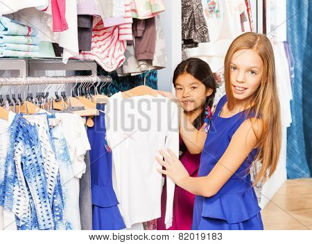 Two girls choosing the right item during shopping