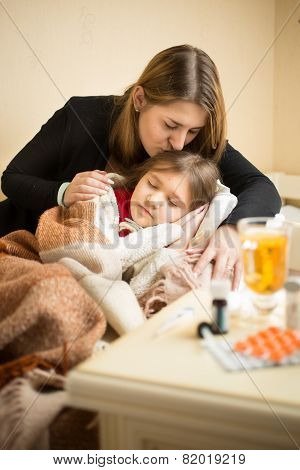 Young Caring Mother Kissing In Head Sick Daughter In Bed