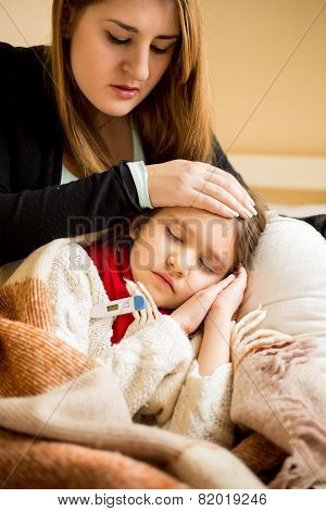 Young Worried Mother Checking Sick Daughters Temperature