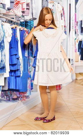 Girl holding and trying white dress on hanger