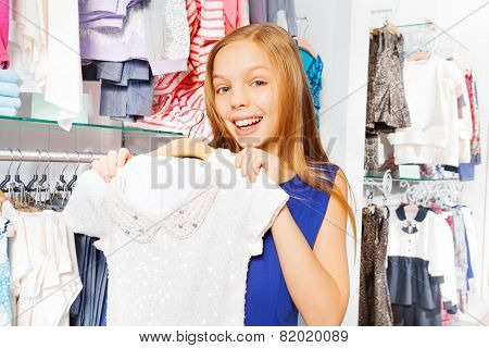 Happy girl with long hair holds dress on hanger
