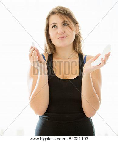 Cute Brunette Woman Choosing Between Menstrual Pad And Tampon