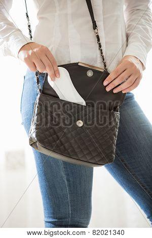 Young Stylish Woman Putting Hygiene Pad In Handbag