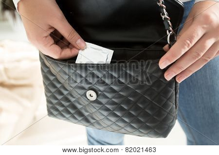 Woman Taking Packed Condom Out Of Purse