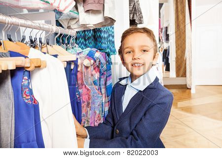 Small boy in navy suit standing near clothes