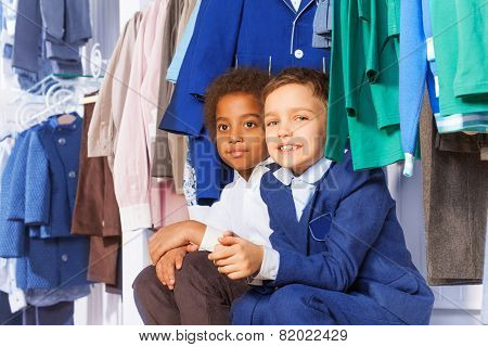 Two small boys sitting near clothes on the hangers