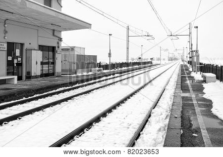 Railroad station in the country, winter landscape with snow. Black and white photo
