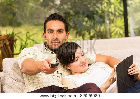 cute couple cuddling in the sofa while watching tv and using tablet