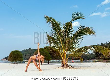 Young woman practicing yoga pose on tne white sand beach