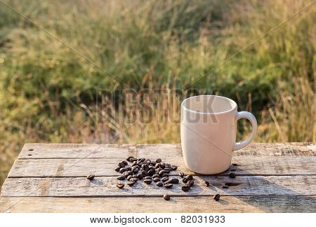 White Coffee Cup And Coffee Beans On Wooden Table At Morning Sunlight