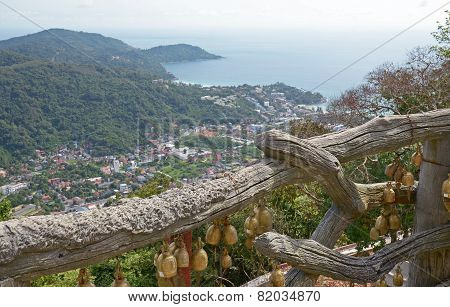 Phuket, Thailand-Sept,23 2014: Wooden fence with Buddhist bells and top view of the coast of Phuket