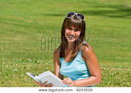 Smiling Young Woman Read Book In Park