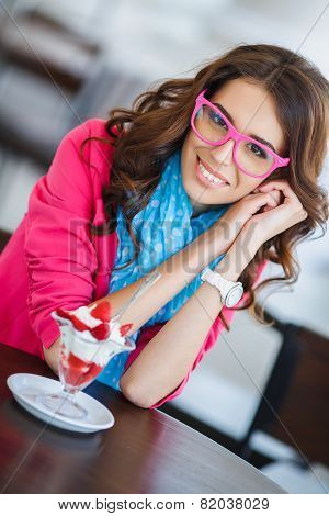 Beautiful young woman at a table in a cafe eating ice cream with strawberries.