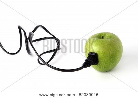 Black plastic electric cable stab in fresh green apple