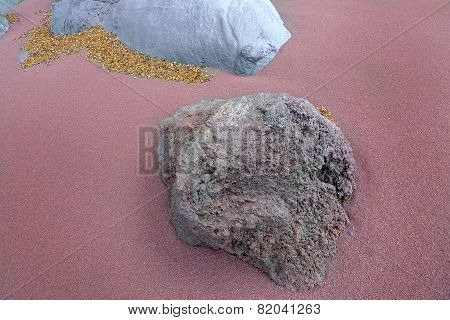 Two gray rocks in the reddish sand