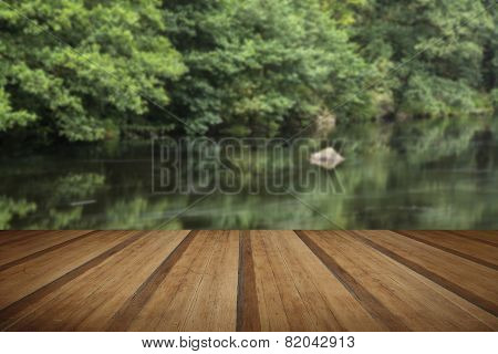 Landscape Long Exposure Of River Flowing Through Lush Green Forest In Summer With Wooden Planks Floo