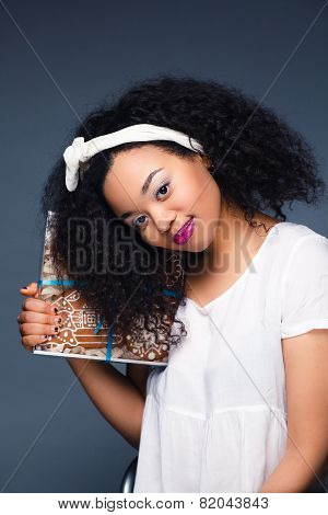 Beautiful happy young woman holding a christmas gift,cookies