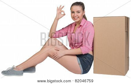Woman sitting next to cardboard box, showing ok sign