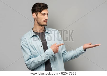 Handsome young man pointing at something