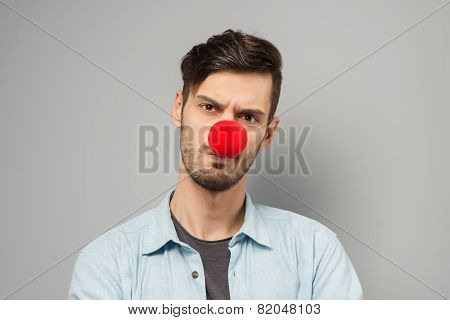 Sad young man with clown nose