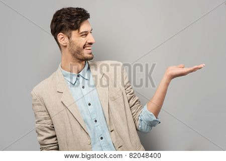 Young man smiling and pointing at something