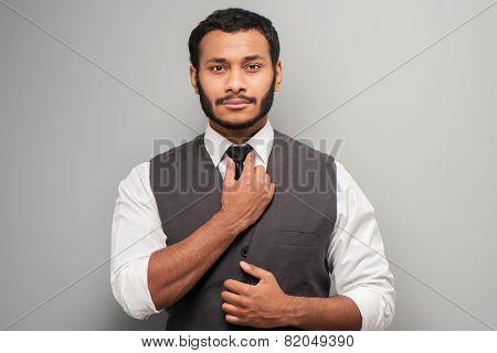 Mixed race man straightening his tie