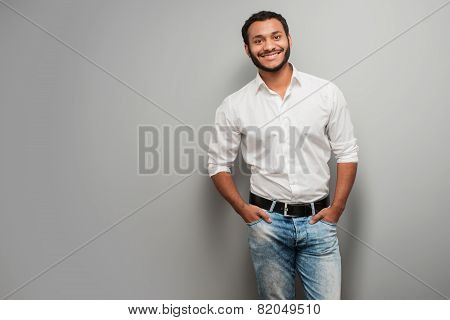 Mixed race man standing on grey background