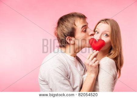 Man kissing girl hiding behind a little red heart