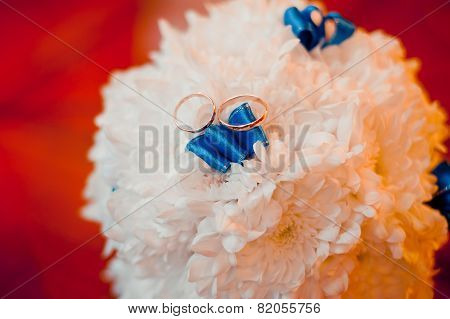 Wedding Rings Lie On A Bouquet Of White With Blue Ribbons