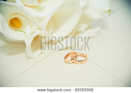 Wedding Rings On The Table On The Background Of The Bride's Bouquet